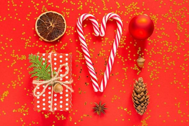 Sfondo vacanza, confezione regalo a pois e palla di natale, anice stellato con cono di abete e ghianda, bastoncino di zucchero natalizio a forma di cuore e agrumi secchi, piatto, vista dall'alto
