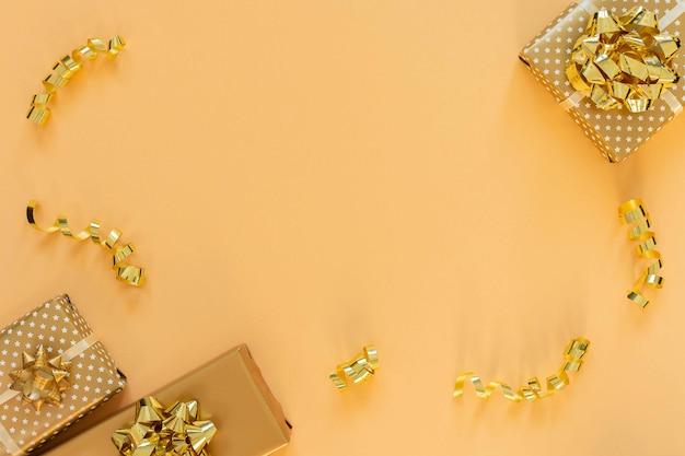 Sfondo vacanza in colori oro, scatole regalo con fiocchi lucidi e con serpentina di nastri glitter su fondo oro, piatto laico, vista dall'alto, spazio di copia