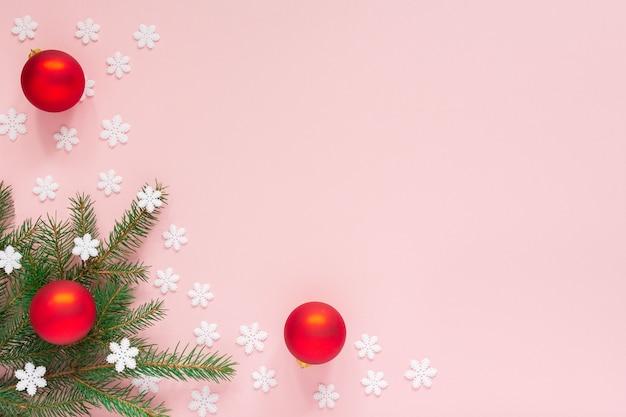 Sfondo vacanza, rami di abete rosso e palle di natale su uno sfondo rosa con fiocchi di neve, vista piana laico e superiore