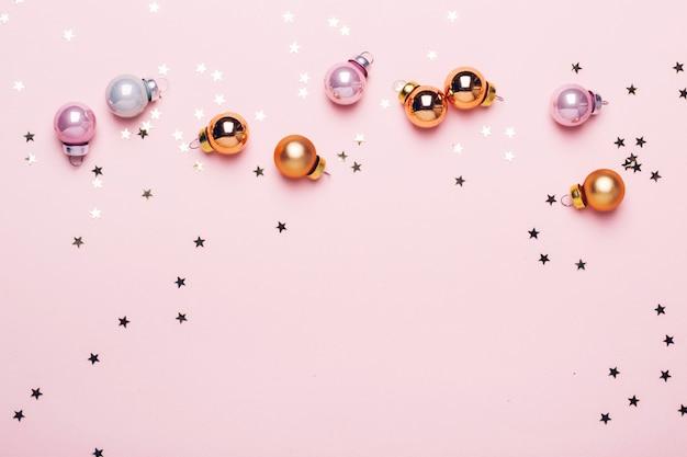 Fondo rosa di natale di festa con le palle e i coriandoli lucidi dorati.