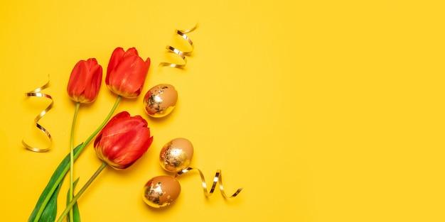 Composizione di festa di due tulipani rossi e uova d'oro con stelle filanti