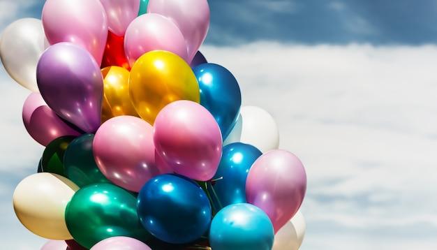 Concetto di vacanza. mazzo di palloncini colorati su uno sfondo di cielo blu