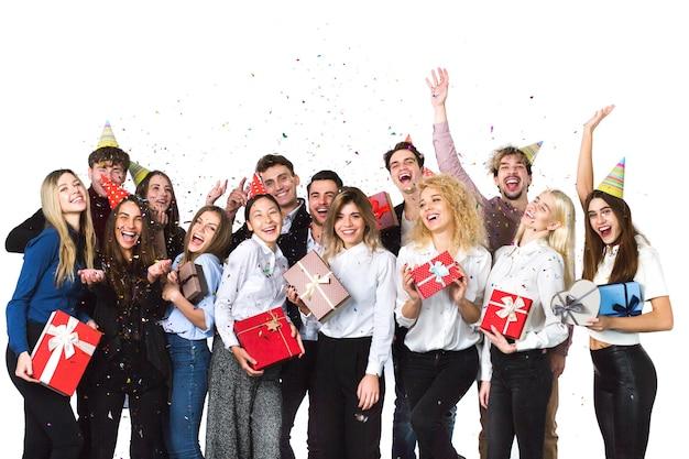 Concetto di vacanza. allegri gioiosi giovani amici in piedi e festeggiano insieme su sfondo bianco.