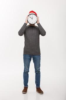 Concetto di festa - giovane uomo bello della barba nascosto dietro l'orologio bianco sopra bianco