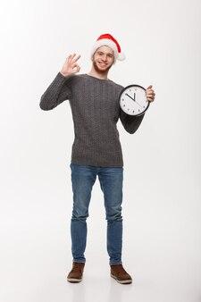 Concetto di vacanza - giovane uomo bello con la barba in maglione con orologio bianco che dà segno giusto.