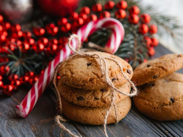 Cucina delle vacanze. concetto di snack alimentari di natale. dolci deliziosi biscotti con scaglie di cioccolato nell'arredamento festivo del nuovo anno di bastoncino di zucchero e cordoncino di perline rosse.