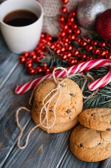 Cucina e pasticceria delle feste. concetto di snack alimentari di natale. dolci deliziosi biscotti con scaglie di cioccolato nell'arredamento festivo del nuovo anno di bastoncino di zucchero e cordoncino di perline rosse.