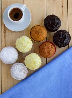 Muffin cupcakes vacanza su molti tipi di fondo in legno e una tazza di caffè. la vista dall'alto.