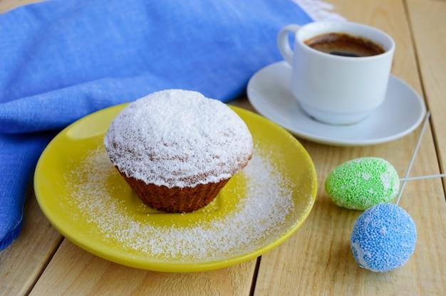 Muffin dei bigné di festa di zucchero a velo su un fondo di legno e una tazza di caffè.