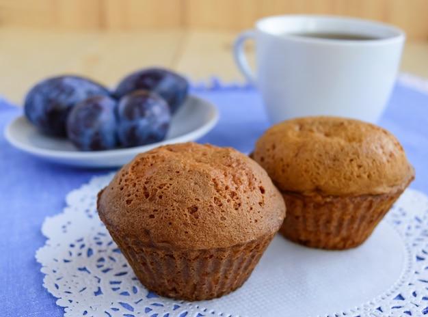 Muffin dei bigné di festa con le prugne su un fondo di legno e una tazza di tè.