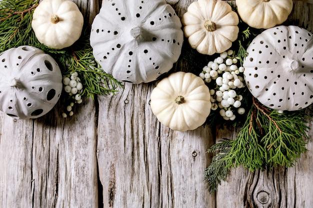 Decorazione festiva con zucche decorative bianche, zucche di argilla artigianale, rami di thuja, bacche su un vecchio tavolo di legno. lay piatto