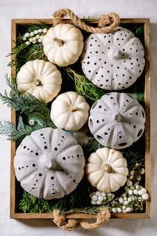 Decorazione festiva con zucche decorative bianche, zucche di argilla artigianale, rami di thuja, bacche in un vecchio vassoio di legno. lay piatto