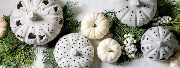 Decorazione festiva con zucche decorative bianche, zucche di argilla artigianale, rami di thuja su un vecchio tavolo di legno. lay piatto. dimensioni banner