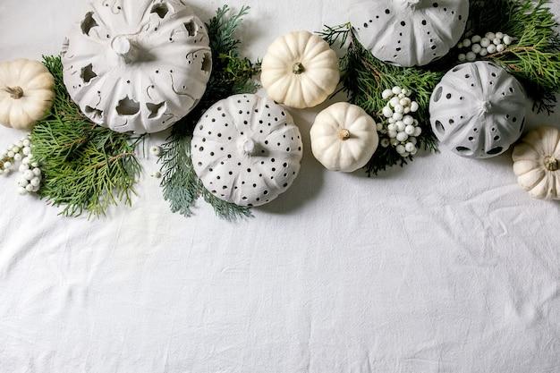Decorazione festiva con zucche decorative bianche, zucche di argilla artigianale, rami di thuja su un vecchio tavolo di legno. lay piatto