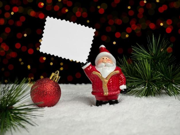 Decorazioni natalizie. il giocattolo dell'albero di natale babbo natale tiene un pezzo di carta con spazio per il testo. sfondo con bokeh. il concetto di natale.