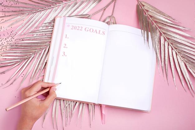 Decorazioni natalizie foglie di palma dorate e un blocco note con una lista dei desideri concetto di pianificazione