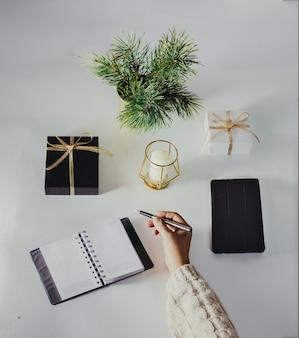 Decorazioni natalizie e taccuino con lista dei desideri su tavolo bianco, stile piatto. concetto di pianificazione.