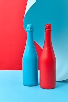 Bottiglie di mock-up dipinte decorative per le vacanze rosse e blu su uno sfondo a due tonalità con un foglio ondulato di carta blu dietro, copia spazio.