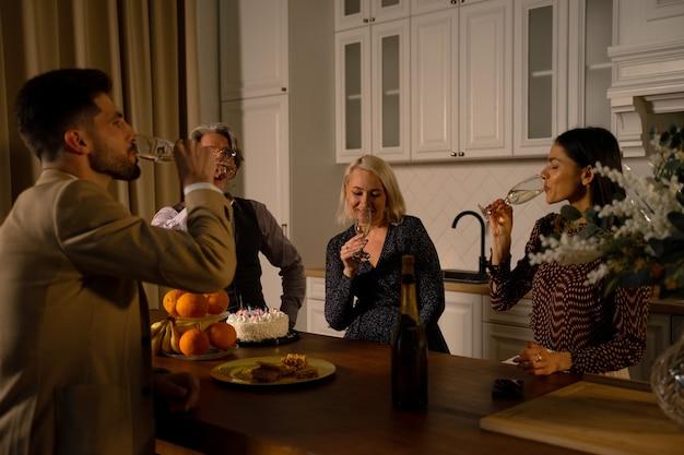 Cena di vacanza giovane coppia e nonni anziani bevendo champagne in cucina