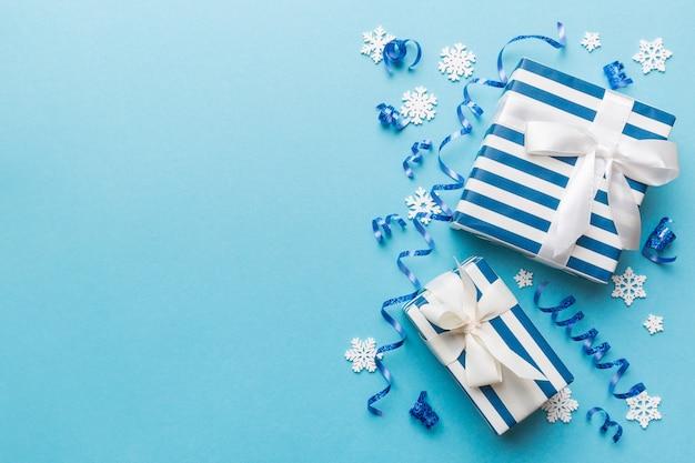 Vacanza piatta con scatole regalo avvolte in carta colorata e legate decorate con coriandoli su sfondo colorato. natale, compleanno, san valentino e concetto di vendita, vista dall'alto.