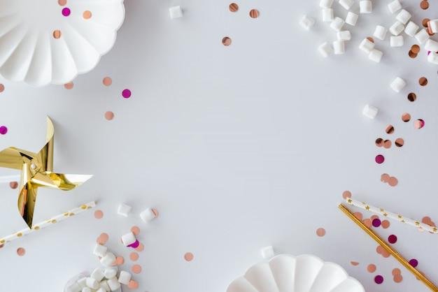Cornice o sfondo di festa con palloncino colorato, regalo, coriandoli, stella d'argento, cappello di carnevale e streamer. stile piatto laico. biglietto di auguri di compleanno o festa con spazio di copia.