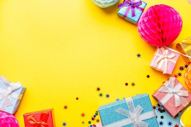 Composizione cornice vacanza con doni e decorazioni su superficie gialla con copia spazio per il testo. celebrazione festosa concetto per cartolina o invito, vista dall'alto, piatto laici