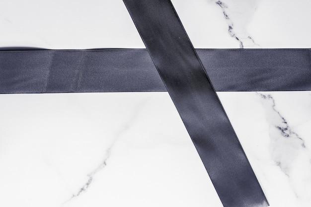 Decorazione regalo di festa e concetto di promozione della vendita nastro di seta nera e fiocco su sfondo marmo f...