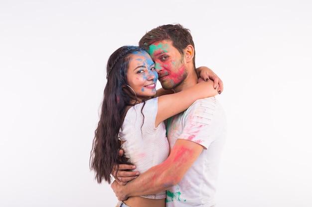 Concetto di vacanza, holi e persone - sorridente divertente donna e uomo in posa con polvere multicolore sui loro volti su sfondo bianco