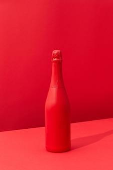 Vacanza mock up bottiglia di champagne verniciato rosso spray su uno sfondo rosso bicolore con ombre morbide, copia spazio. concetto minimo.