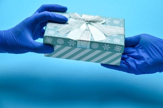 Una vacanza in una pandemia un uomo in guanti medici passa un regalo congratulazioni ai medici