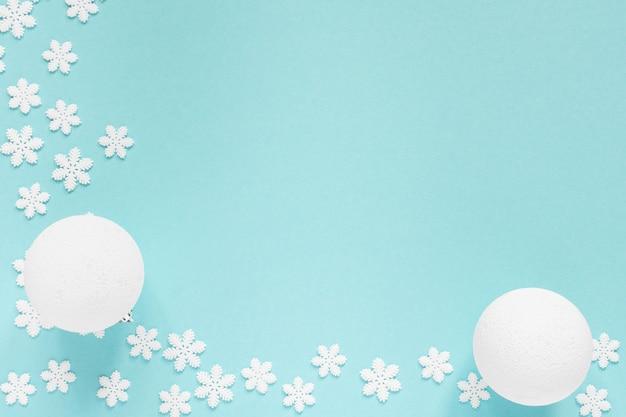 Sfondo pastello festivo, fiocchi di neve bianchi e palla di natale su uno sfondo blu delicato, vista piatta laico