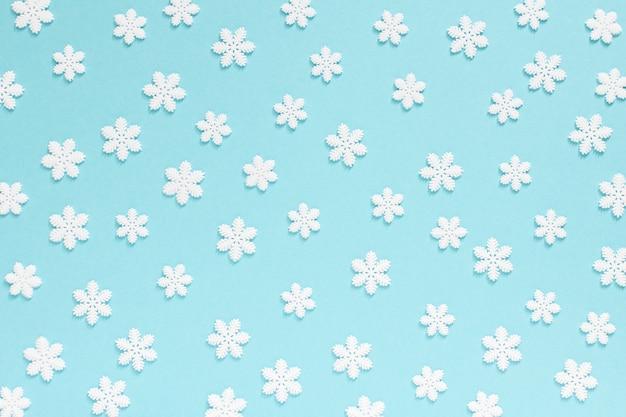 Holiday sfondo pastello, fiocchi di neve bianchi su uno sfondo blu delicato, piatto laico, vista dall'alto
