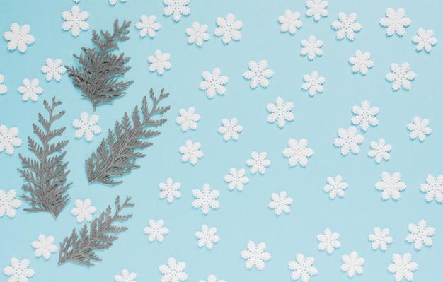 Sfondo pastello festivo, fiocchi di neve bianchi e ramoscelli di thuja su uno sfondo blu delicato, vista piatta e dall'alto