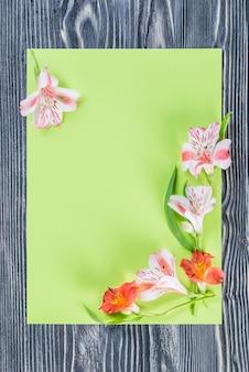 Cartolina di festa con foglio di carta vuoto e fiori, parete floreale