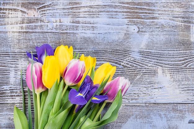 Cartolina di festa con i fiori del tulipano sulla superficie di legno colorata, bordo floreale