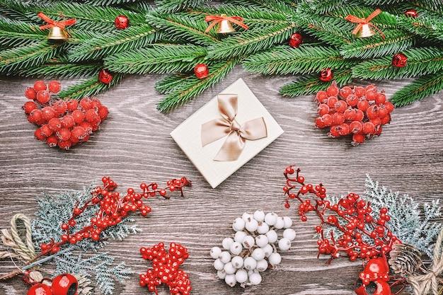 Sfondo di vacanza con auguri di stagione e bordo di rami di albero di natale dall'aspetto realistico decorati con bacche.