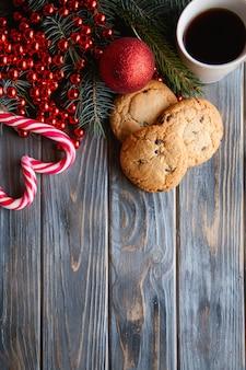 Decorazione stagionale di festa su fondo di legno. biscotti con gocce di cioccolato e bastoncini di zucchero a forma di cuore. concetto di alimenti di natale.