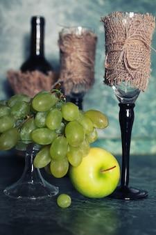Bottiglia di vino fissata per le vacanze con uva verde sullo sfondo