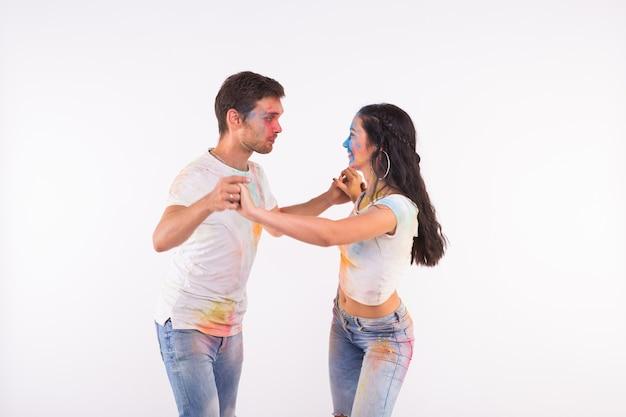 Vacanze, danza sociale, holi e concetto di persone - coppia felice che balla bachata o kizomba con polvere multicolore sui loro volti su sfondo bianco