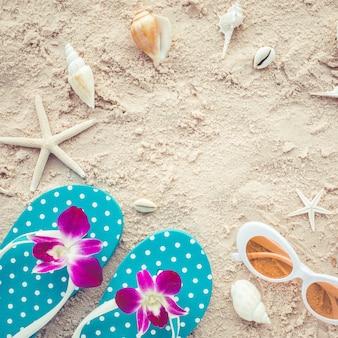 Concetto di vacanza estiva con sandali e occhiali da sole e conchiglie su sfondo spiaggia.