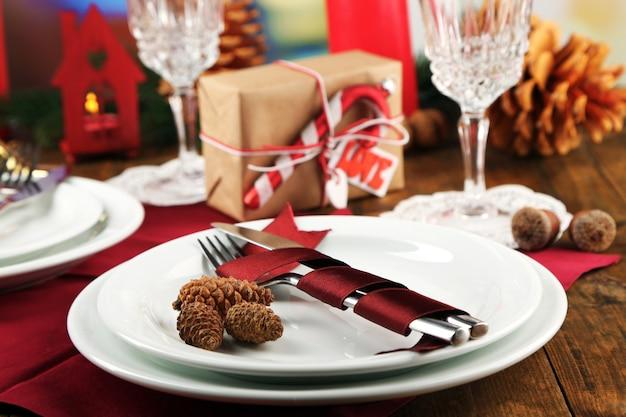 Impostazione della tavola delle vacanze con sfondo di decorazioni natalizie
