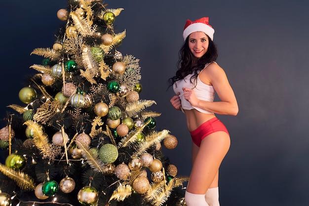 Vacanze e concetto di celebrazione - felice donna bruna con il cappello di babbo natale decora un albero di natale a casa in soggiorno, pantaloni rossi