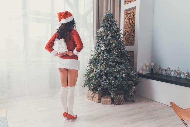Vacanze e concetto di celebrazione - felice donna bruna con il cappello di babbo natale decora un albero di natale a casa nel soggiorno