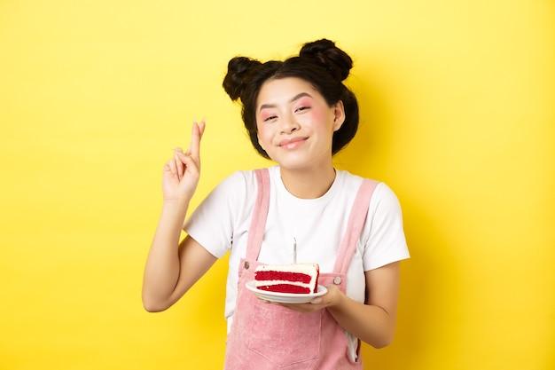Feste e celebrazioni. la ragazza asiatica positiva di compleanno incrocia le dita, esprimendo il desiderio con la torta del b-day e la candela accesa, sorridendo felice alla macchina fotografica, giallo