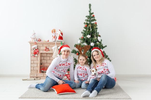 Vacanze e concetto festivo. ritratto di famiglia felice dall'albero di natale