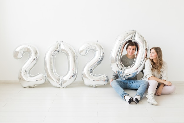 Concetto festivo, festivo e festivo - coppia divertente seduto su un pavimento vicino a palloncini argento 2020. festa di capodanno