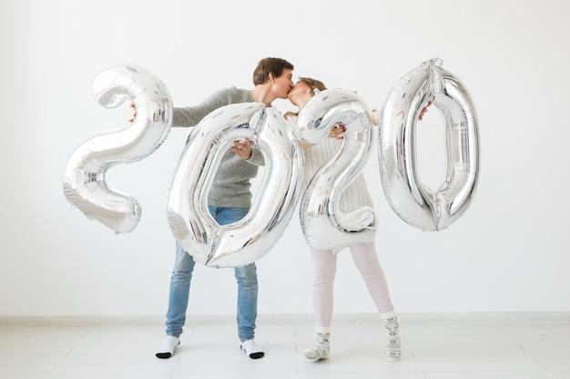 Concetto di feste, festività e festa - felice coppia di innamorati baci e detiene palloncini argento 2020 festa di capodanno
