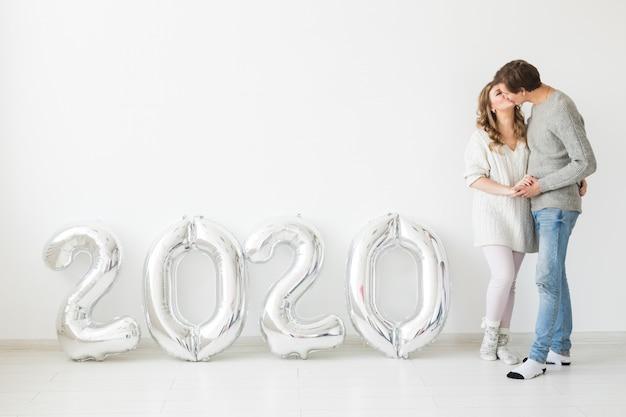 Concetto di feste, festività e festa - felice coppia di innamorati vicino palloncini argento 2020. festa di capodanno