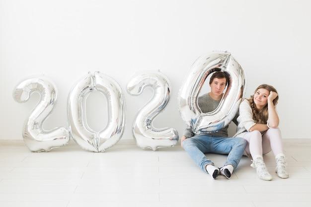 Feste, concetto festivo e del partito - coppie amorose felici che si siedono su un pavimento vicino ai palloni d'argento 2020. festa di capodanno