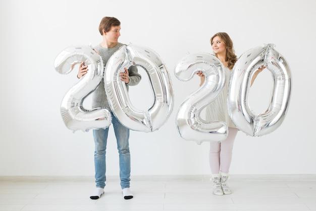Feste, festività e concetto di festa - felice amorevole coppia divertente detiene palloncini argento 2020. festa di capodanno